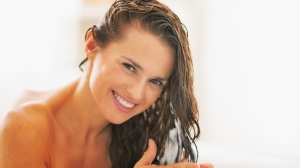 Happy-young-woman-applying-hair-conditioner